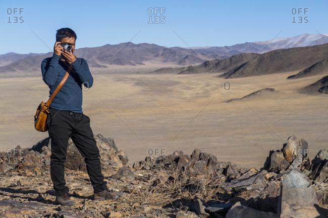 Man photographing barren landscape, Olgiy, Bayan-Olgiy, Mongolia