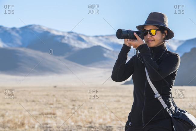 Woman photographing barren landscape, Olgiy, Bayan-Olgiy, Mongolia