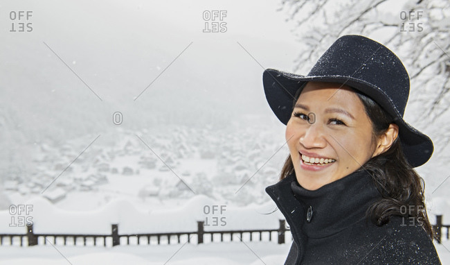 portrait of a smiling woman above the village of Shirakawa on a snowy winters day