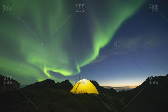 Northern Lights - Aurora Borealis fill sky over yellow tent, Muskiness, Loftin Islands, Norway