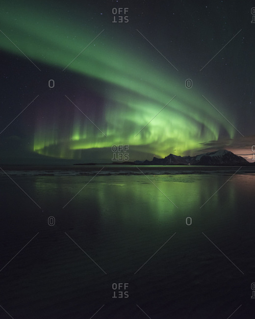 Northern Lights reflect on beach in winter,  Loftin Islands, Norway
