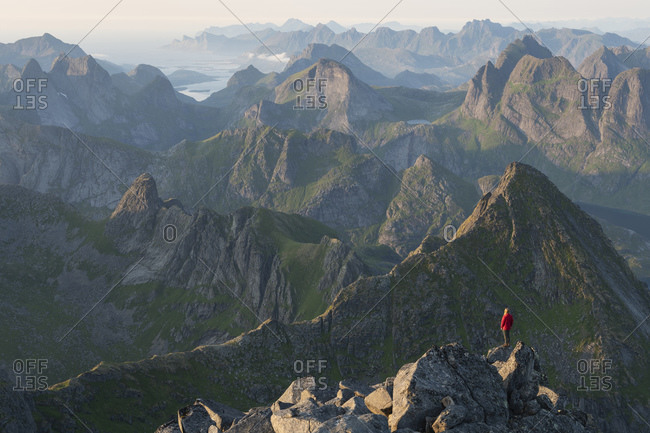 Hiker on rocky summit of Hermannsdalstind with mountains in the distance, Loftin Islands, Norway