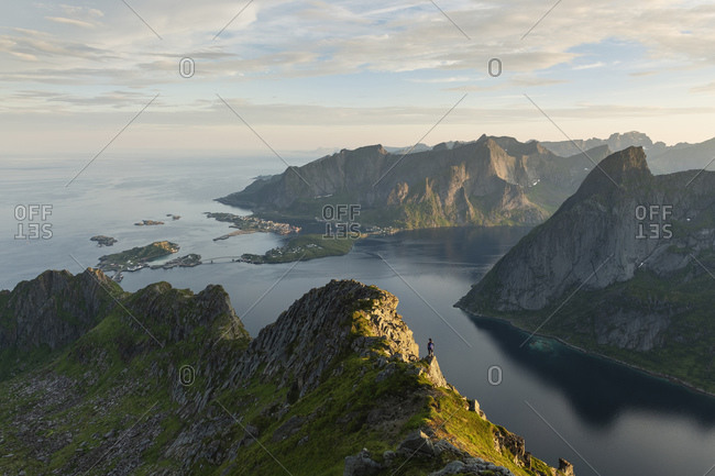 Female hiker on mountain ridge with Reine and Reinefjord in the background, Loftin Islands, Norway