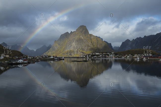 Rainbow rises into sky over Olstind mountain peak, Reine, Loftin Islands, Norway