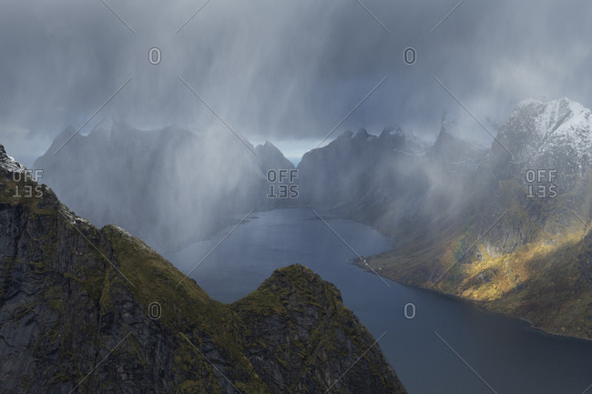 Autumn snow flurries fall over mountain peaks with view towards Kirkefjord from Reinebringen mountain peak, Muskinessoy, Loftin Islands, Norway