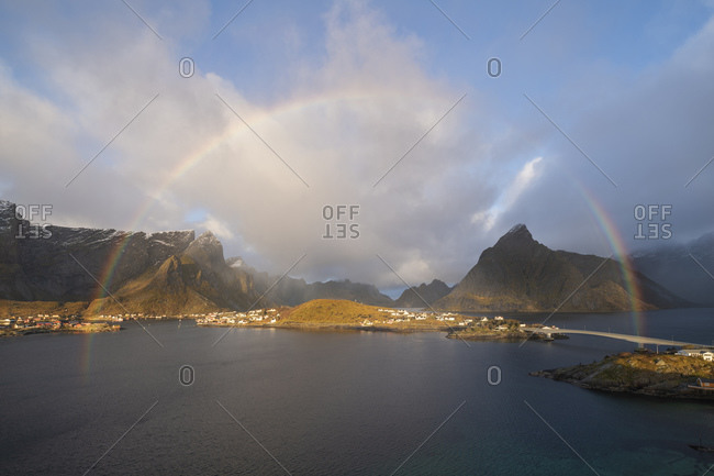 Autumn rainbow fills sky over Reine and surrounding mountains, Muskiness¸y, Loftin Islands, Norway