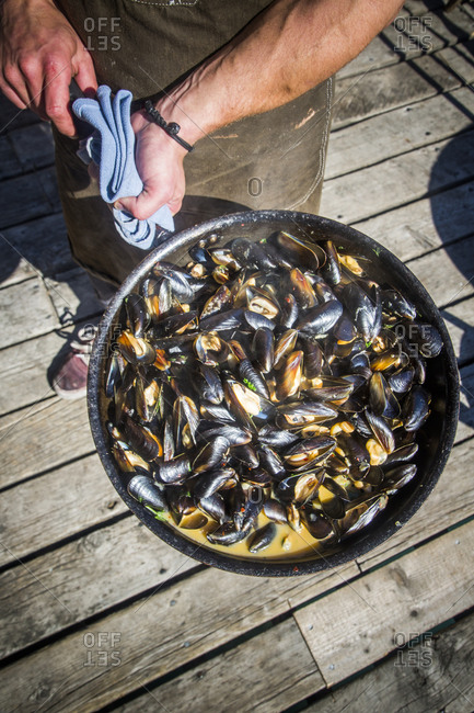 A man holds a pan full of muscles at a restaurant in Halibut Cove, Alaska.