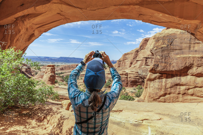 A female hiker taking a photograph under Tower Arch.