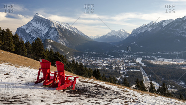 Two red chairs overlooking distant town, Alberta, Canada