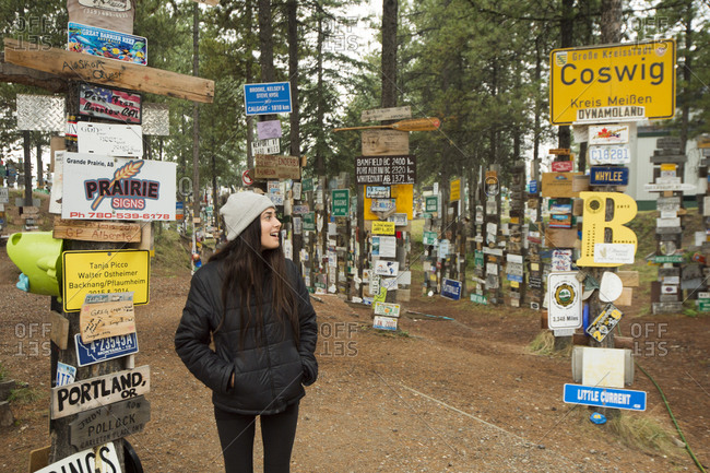 Canada, British Columbia, Alaska Highway - August 8, 2018: Woman visiting Sign Post Forest, British Columbia, Canada