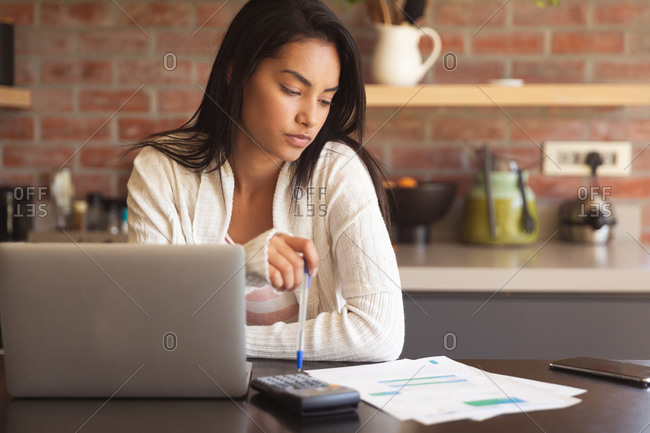 Mixed race woman spending time at home self isolating and social distancing in quarantine lockdown during coronavirus covid 19 epidemic, working from home using laptop computer in kitchen.