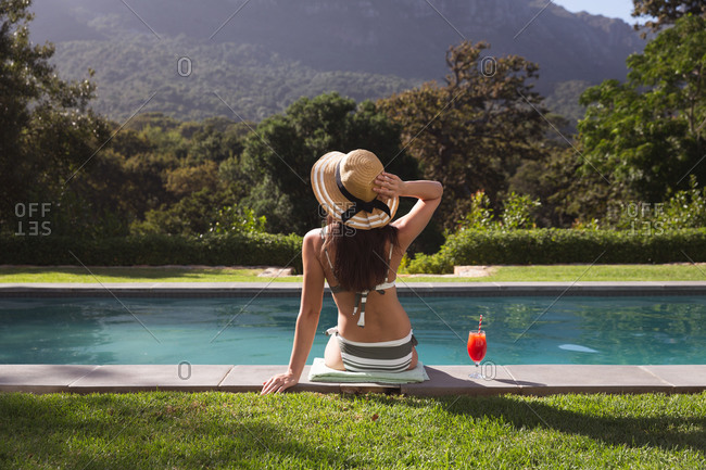 Rear view of mixed race woman spending time by pool self isolating and social distancing in quarantine lockdown during coronavirus covid 19 epidemic, sitting by a swimming pool in a garden.