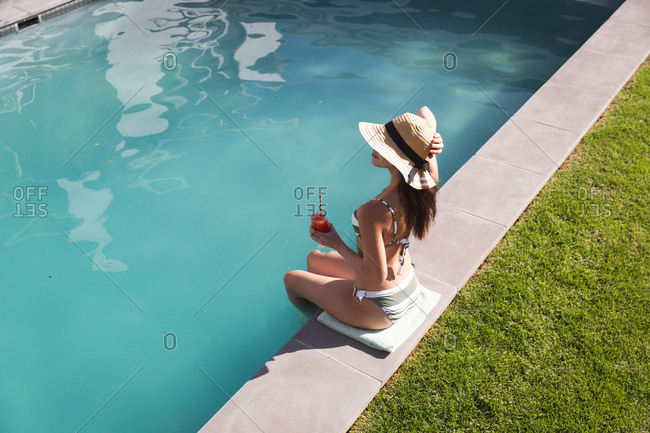 Mixed race woman spending time by swimming pool self isolating and social distancing in quarantine lockdown during coronavirus covid 19 epidemic, sitting by a swimming pool holding a drink.