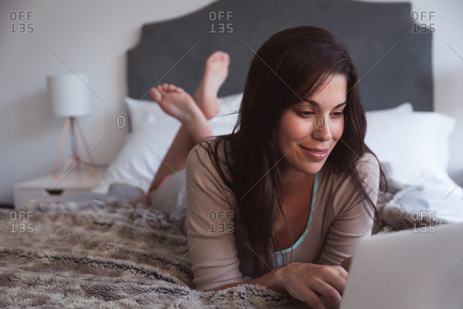 Mixed race woman spending time at home self isolating and social distancing in quarantine lockdown during coronavirus covid 19 epidemic, lying on bed using laptop in bedroom.