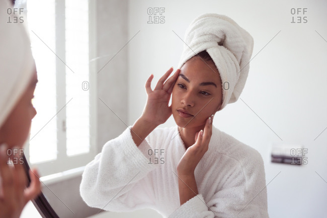 Mixed race woman spending time at home self isolating and social distancing in quarantine lockdown during coronavirus covid 19 epidemic, looking at mirror taking care of her skin in bathroom.
