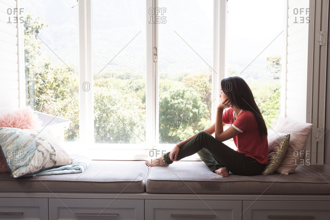 Mixed race woman spending time at home self isolating and social distancing in quarantine lockdown during coronavirus covid 19 epidemic, sitting on window seat looking out of window in sitting room.