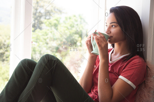 Mixed race woman spending time at home self isolating and social distancing in quarantine lockdown during coronavirus covid 19 epidemic, sitting on window seat drinking coffee in sitting room.