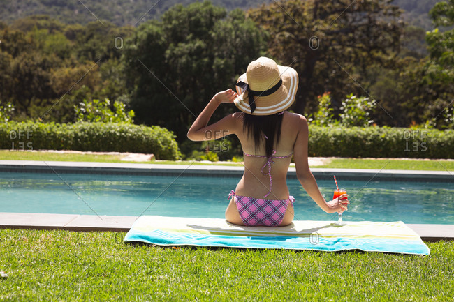 Rear view of mixed race woman spending time by pool self isolating and social distancing in quarantine lockdown during coronavirus covid 19 epidemic, sitting by a swimming pool holding a drink.