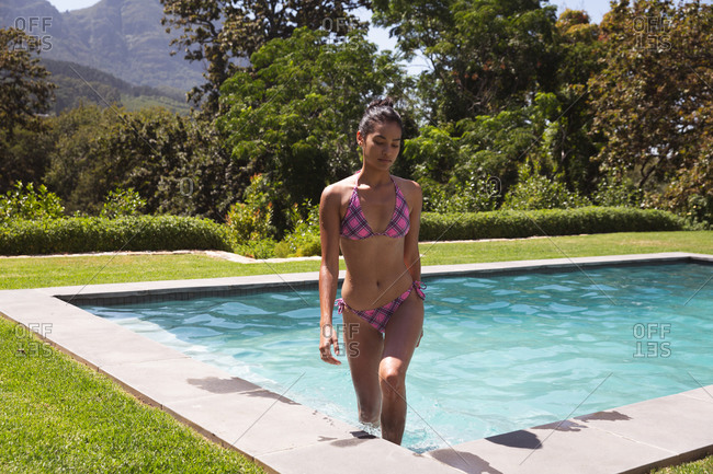 Mixed race woman spending time by swimming pool self isolating and social distancing in quarantine lockdown during coronavirus covid 19 epidemic, walking out of the pool
