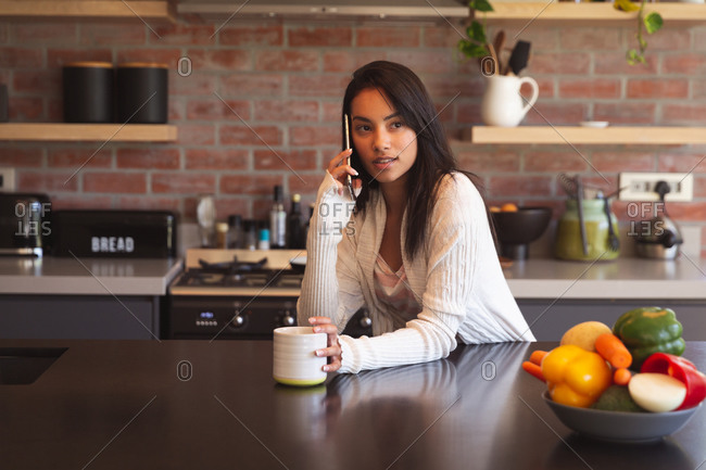 Mixed race woman spending time at home self isolating and social distancing in quarantine lockdown during coronavirus covid 19 epidemic, talking on the smartphone and drinking coffee in kitchen
