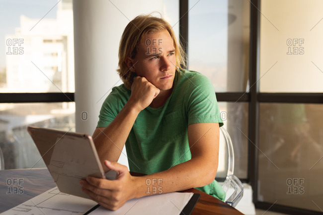 Caucasian man sitting by a table, using a digital tablet and looking away. Social distancing and self isolation in quarantine lockdown.