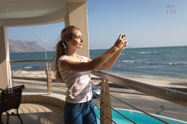 Caucasian woman standing on a balcony, holding a smartphone and taking a selfie. Social distancing and self isolation in quarantine lockdown.