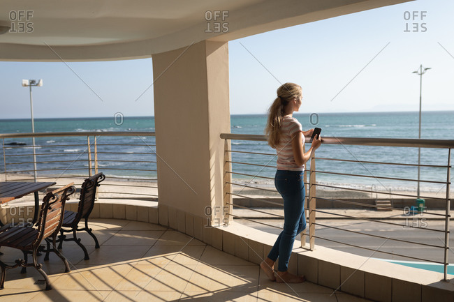 Caucasian woman standing on a balcony, holding a smartphone and looking away. Social distancing and self isolation in quarantine lockdown.