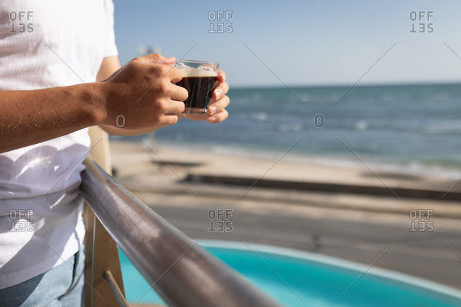 Mid section view of a Caucasian man standing on a balcony, holding a cup of coffee. Social distancing and self isolation in quarantine lockdown.
