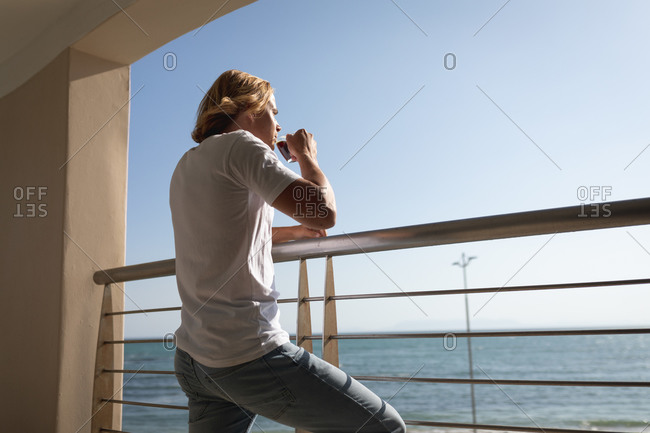 Caucasien man standing on a balcony, drinking a cup of coffee. Social distancing and self isolation in quarantine lockdown.