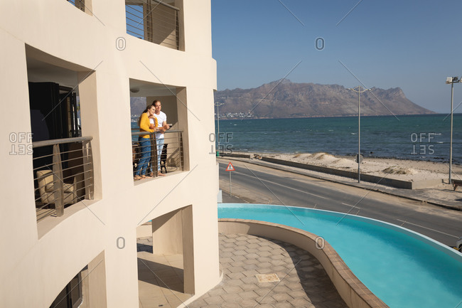 Caucasian couple standing on a balcony, embracing. Social distancing and self isolation in quarantine lockdown.