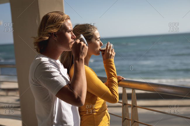 Caucasian couple standing on a balcony, drinking coffee. Social distancing and self isolation in quarantine lockdown.