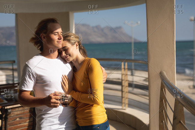 Caucasian couple standing on a balcony, embracing and holding a cup of coffee. Social distancing and self isolation in quarantine lockdown.