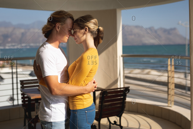 Caucasian couple standing on a balcony, embracing and touching each other foreheads. Social distancing and self isolation in quarantine lockdown.