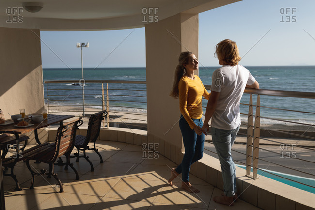 Caucasian couple standing on a balcony, holding hands. Social distancing and self isolation in quarantine lockdown.