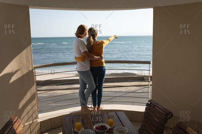 Caucasian couple standing on a balcony, embracing and pointing at the sea. Social distancing and self isolation in quarantine lockdown.