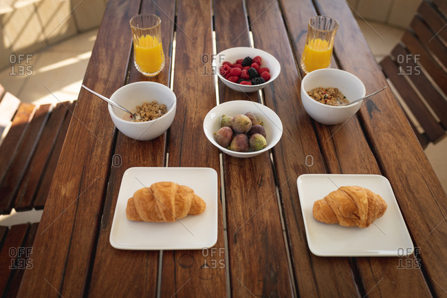 Breakfast lying on a table. Two croissants, two bowls of oatmeal, two glasses of juice, a bowl of figs and a bowl of fruits.