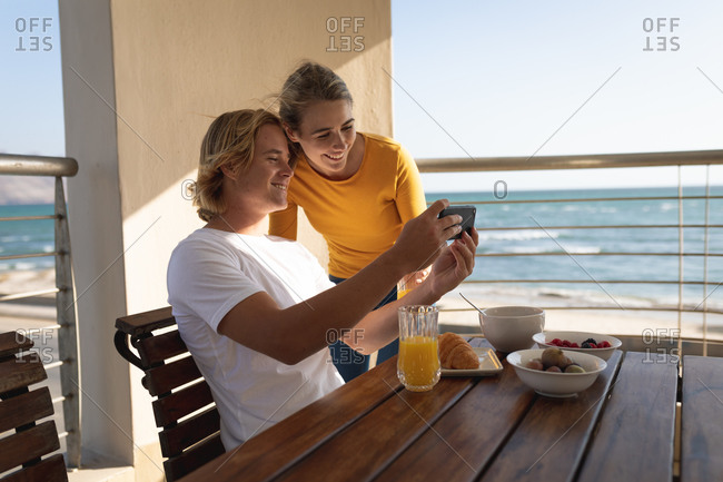 Caucasian couple sitting and standing by a table, a man is showing a woman something on his smartphone. Social distancing and self isolation in quarantine lockdown.