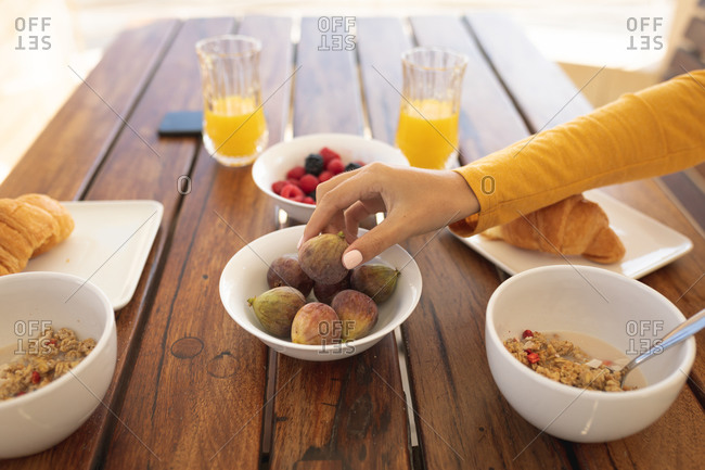 Caucasian woman sitting by a table, eating breakfast, reaching for a fig. Social distancing and self isolation in quarantine lockdown.
