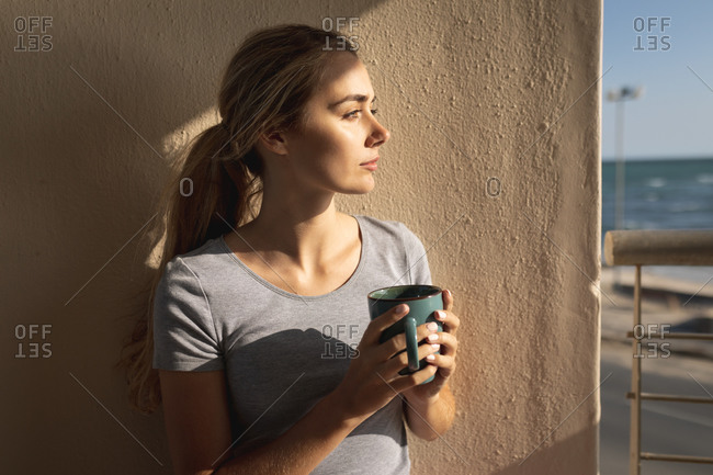 Caucasian woman standing on a balcony, holding a cup of coffee and looking away. Social distancing and self isolation in quarantine lockdown.