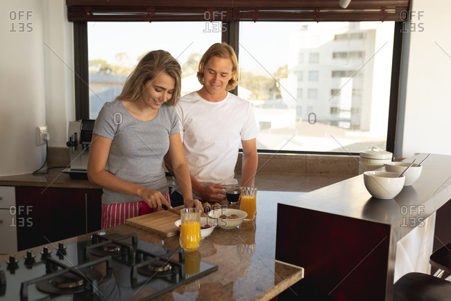 Caucasian couple standing in a kitchen, making breakfast together. Social distancing and self isolation in quarantine lockdown.