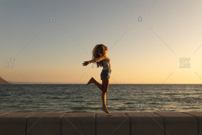 Caucasian woman on holiday enjoying her time on a beach promenade during a sunset, jumping and spreading her arms, the sun setting over the sea in the background