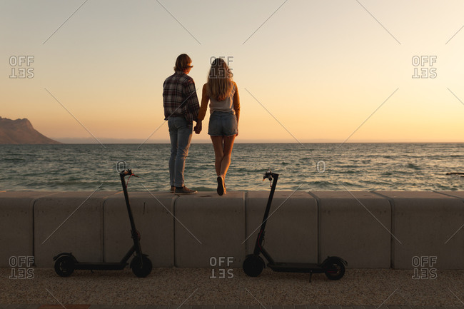Caucasian couple standing on a promenade during sunset, holding hands and looking at the sea