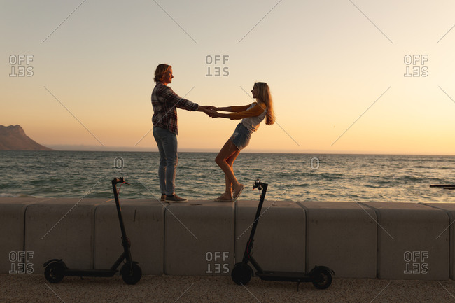 Caucasian couple dancing and spinning on a promenade during sunset, holding hands and looking at each other