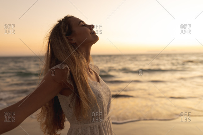 Caucasian woman standing barefoot on a beach during sunset, spreading her arms with eyes closed