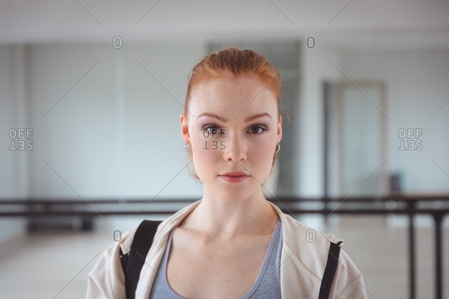 Caucasian attractive female ballet dancer with red hair wearing sportswear, entering a studio, preparing for a ballet class, looking into the camera.