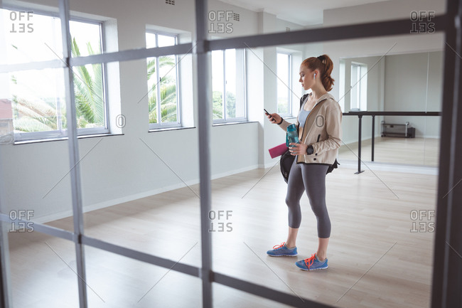 Caucasian attractive female ballet dancer with red hair wearing sportswear, entering a studio, preparing for a ballet class, looking at her phone with earphones in.
