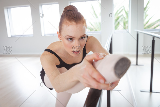 Caucasian attractive female ballet dancer with red hair stretching her leg, preparing for a ballet class in a bright studio, focusing on her exercise.