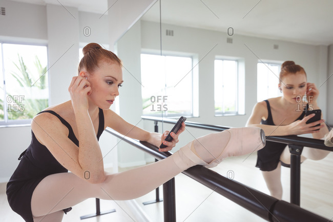 Caucasian attractive female ballet dancer with red hair holding a barre, preparing for a ballet class in a bright studio, stretching her leg and using her smartphone next to a mirror.