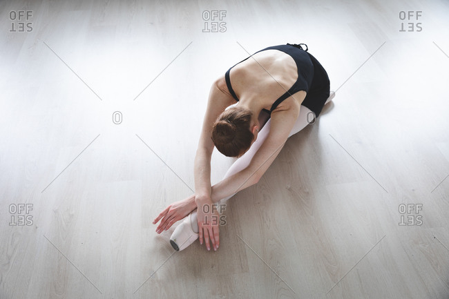 Overhead view of a Caucasian attractive female ballet dancer with red hair stretching out, preparing for a ballet class in a bright studio, focusing on her exercise, sitting on the floor.