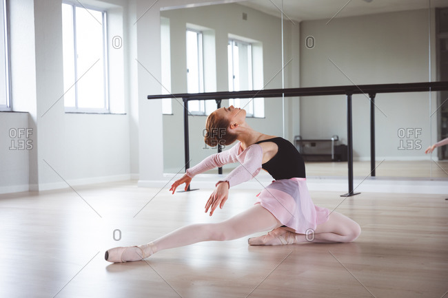 Caucasian attractive female ballet dancer with red hair stretching out, preparing for a ballet class in a bright studio, focusing on her exercise, sitting on the floor.